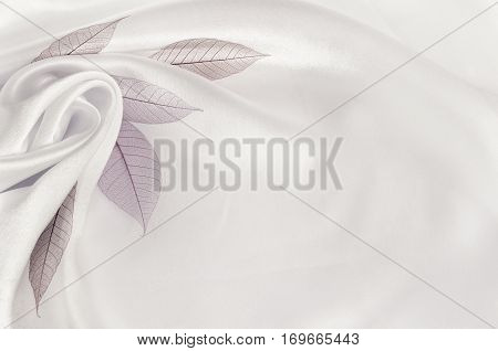 White silk background with flower drapery and leaves