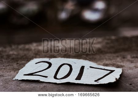 closeup of a piece of paper with the number 2017, as the new year, written in it on the ground