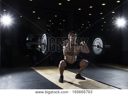 Muscular sportsman doing the front squat exercise in the gym at crossfit training.