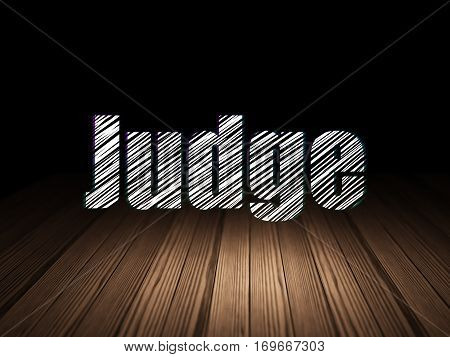 Law concept: Glowing text Judge in grunge dark room with Wooden Floor, black background