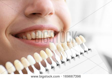 Young woman at dentist office checking and selecting colour of the teeth
