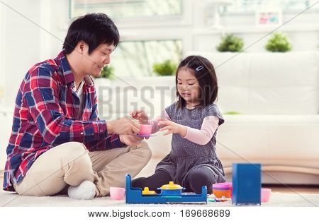 Young  Happy Father Playing With His Cute Little Daughter At Home