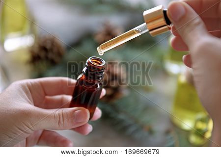 Woman filling in bottle with pine essential oil