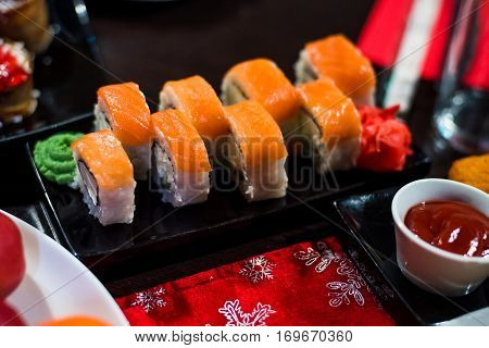 rolls with fish and avocado on a plate with sauce, ginger and wasabi