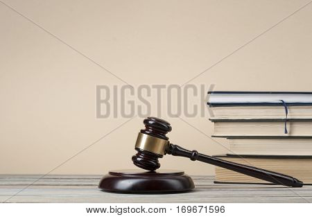 Books with wooden judges gavel on table in a courtroom office