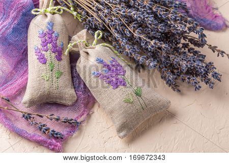 Two aromatic embroidered sachets filled with dried lavender and a bouquet of dry lavender