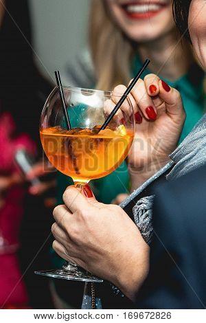woman holds orange margareta fresh Cocktail in bar