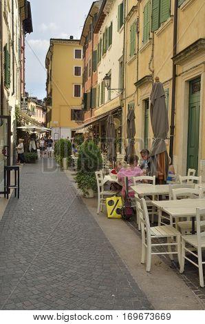 PESCHIERA DEL GARDA, ITALY - AUGUST 7, 2014: Outdoors restaurants in street of Peschiera a village of Garda Lake and belong to the province of Verona in Veneto Italy.