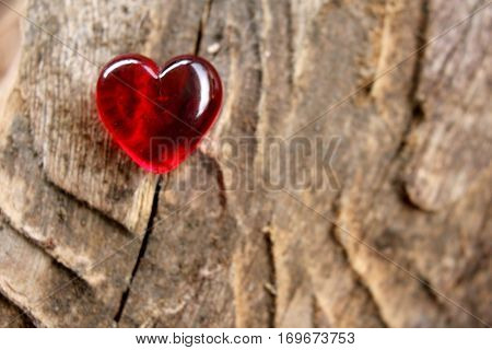 Red Glass Heart on soft focus timber background