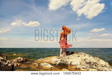 romantic redhead young woman in a dress on the ocean coast. girl in the summer outdoors. concept of freedom, inspiration and dreams. sea and sky