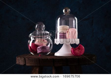 Colorful Tasty Macaroons In Glass Jars On Dark Blue Wall Background