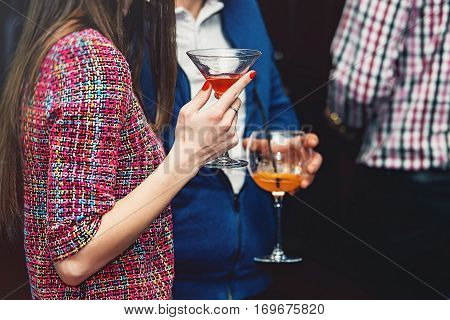 young woman holds drink in a bar