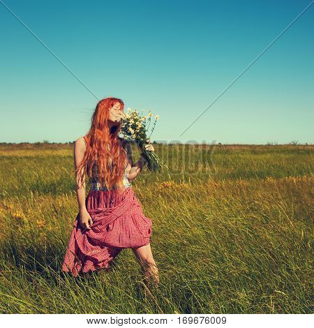 redhead woman with a bouquet of flowers in a dress outdoors. Beautiful stylish romantic young girl on nature background. field and clear cloudless sky