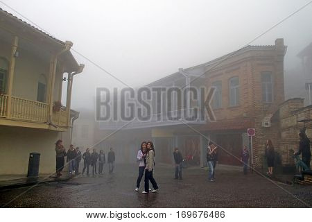 SIGHNAGHI, GEORGIA - OCTOBER 10, 2010: Teenagers are on the excursion in Sighnaghi in foggy weather, Georgia. Sighnaghi is a town in Georgia's easternmost region of Kakheti and the administrative center of the Sighnaghi Municipality