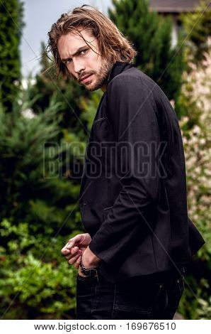 Elegant long hairs handsome man poses outdoor.