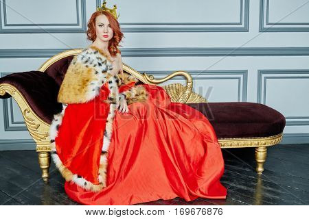 Red-haired woman in red dress, cloak and with crown on head sits on couch.