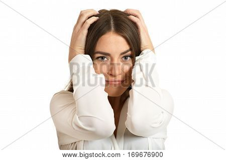 Portrait of frustrated brunette woman holding head in hands isolated on white background