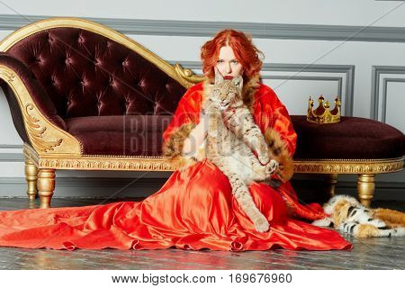 Red-haired woman in red dress, cloak sits on floor near couch holding lynx cub.