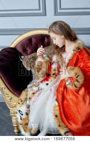 Girl in red cloak with crown on head sits on couch playing with lynx cub.