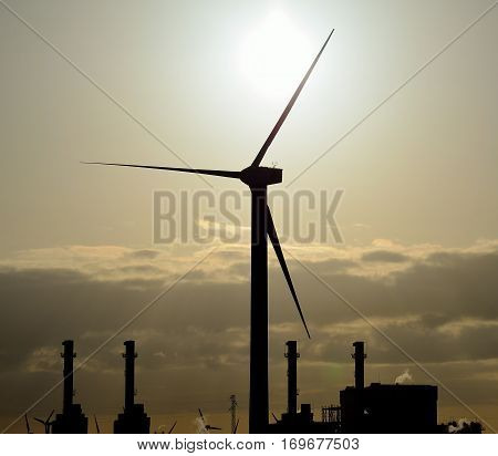 Wind turbine in foreground and power plant in background at sunrise
