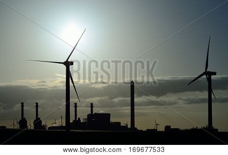 Wind turbines and power plant with intense sun at dawn