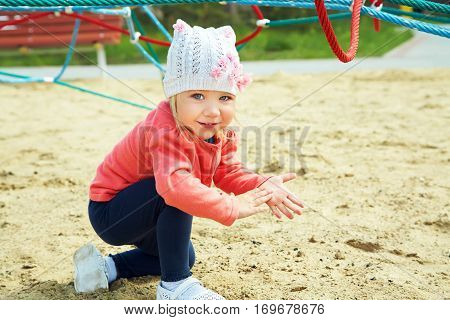 Active cute little girl on playground. child playing in the open air in the summer