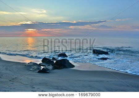 Pastel Colored Sunrise Over Rock Jetty at the Beach