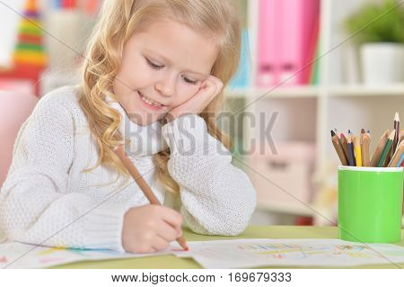 Portrait of a cute little girl drawing and dreaming