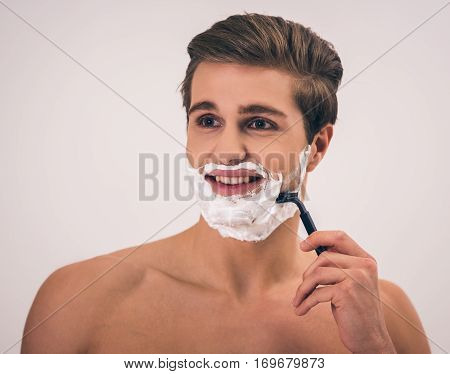 Handsome young naked man with shaving foam on his face is looking away and shaving on gray background