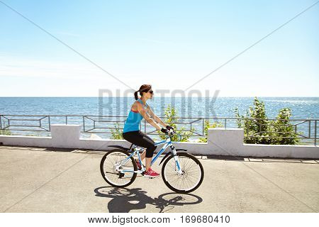 young woman riding a bike along the coast. Active people outdoors. sport lifestyle