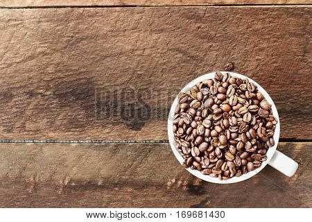 Overhead shot of a white cup filled with whole fresh coffee beans over a wood table top. Flat lay top view style.