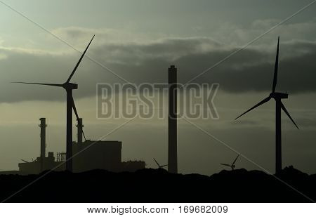 Power plant and wind turbines backlit at dawn