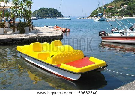 PAXOS, GREECE - JUNE 10, 2014: A bright yellow pedalo moored in the harbour at Lakka on the Greek island of Paxos. Just 13km long, the small Ionian island has a population of circa 2300.