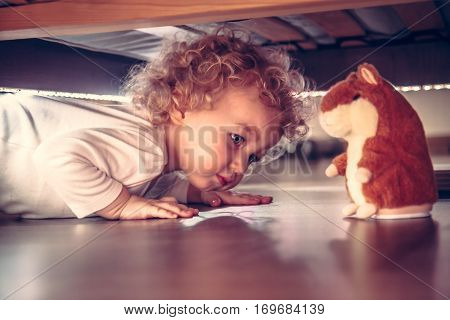 Funny cute curious baby playing under the bed with toy hamster in vintage style