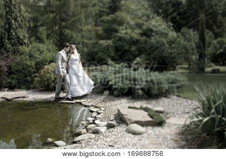 Bride and groom walking near lake in the beautiful park