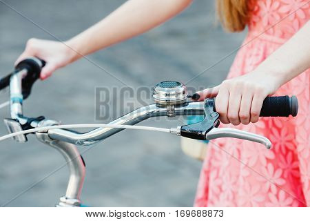 Close up hands of a young girl on vintage bicycle handlebar