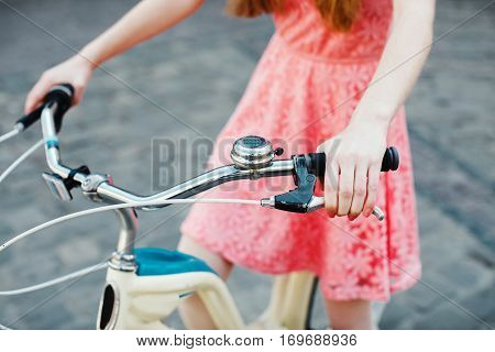 Close up hands of a young girl in pink dress, holding handbrake on vintage bicycle