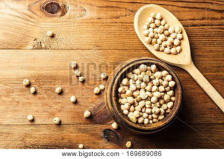 Portion of Chick Peas in wooden bowl with spoon top view