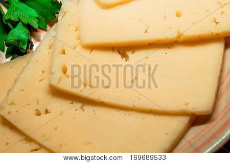 Sliced cheese lying on a plate with greens.