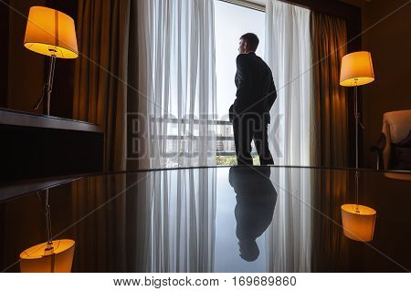 man stands in hotel room back to the camera and looks out over the city. man and lamps reflected in glass table.