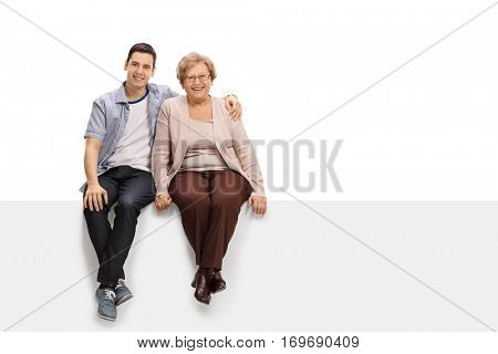 Happy young man and a mature woman sitting together on a panel isolated on white background