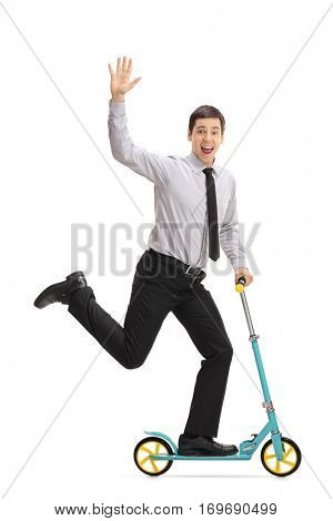 Full length portrait of an overjoyed young businessman riding a scooter wand waving isolated on white background
