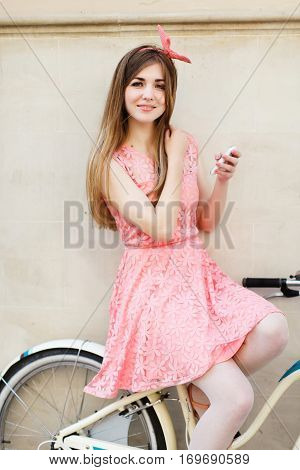 Sensual pretty blonde girl sitting on bicycle with mobile phone. Young woman with blond-brown long hair, wearing pink head wrap and pink dress with a pattern of flowers.