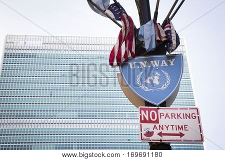 NEW YORK - APR 30 2016: The UN Way street sign and flags on a pole across from the United Nations building above Ralph Bunche Park in Tudor City across 1st Avenue on the East side of Manhattan.
