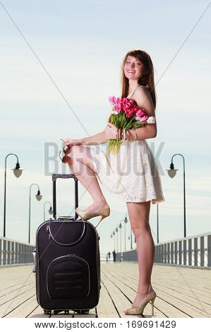 Travel voyage adventure packing concept. Woman wearing short white dress standing one leg in high heels on big suitcase holding bouquet of tulips. Pier in background