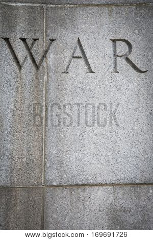Close up of the word War from the Bible verse Isaiah 2:4 inscribed into the granite wall across from the United Nations building in Ralph Bunche Park across 1st Avenue on the East side of Manhattan.