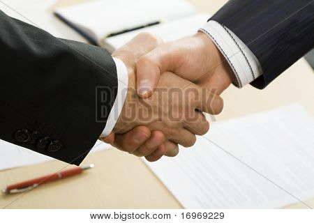 Photo of business handshake over workplace