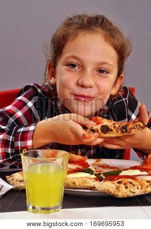 Little girl eating pizza and orange soda.