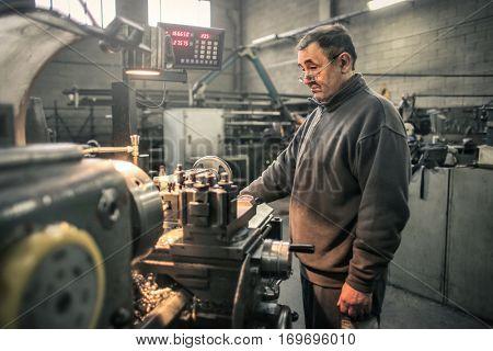 Worker standng in front of huge industrial machine