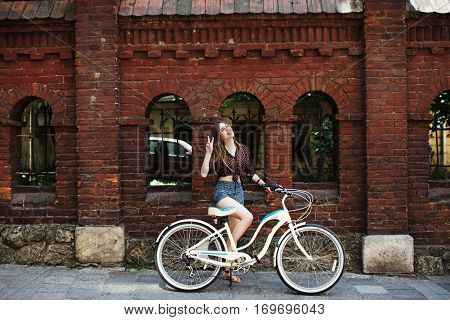 Pretty girl with long fair hair wearing on dark blouse and blue shorts with bicycle have fun on the brick wall background, on the old city street